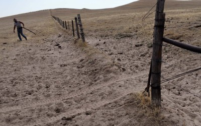 Hay Springs, Nebraska August 27, 2012  Jim Mracek, a caretaker of a 5,000 acre cattle ranch stricken by the drought, closes a fence on his way to round up the cows and their calves.