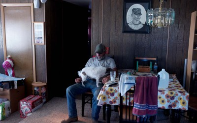 Hay Springs, Nebraska August 31. 2012  Jim Mracek sits in the living room of his trailer during another rainless day of 102 degree tempertures. Jim is a caretaker on a 5,000 acre cattle ranch in Western Nebraska. A drawing of his son, Cory, who was killed in Iraq, hangs on the wall.