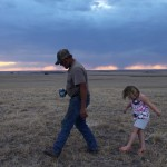 Hay Springs, Nebraska.September 2, 2012..On an evening stroll, Jim Mracek leads his grandaughter across the drought stricken fields of the cattle ranch that he looks after, keeping an eye out for burrs because she is wearing sandals.