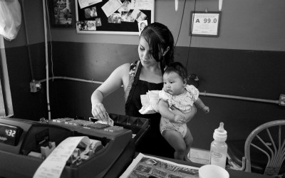 North Carolina September 2011  A young woman holds her niece as she works the cash register at her parents restaurant.