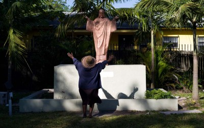 A woman prays to a statue of Jesus out in the yard of Notre Dame d'Haiti in Miami's Little Haiti neighborhood on  a sunny morning on January 3, 2013, a few days after the New Year.  Members of the Catholic church, where masses are given in the Creole language, come often to spend time in the large yard and pray.