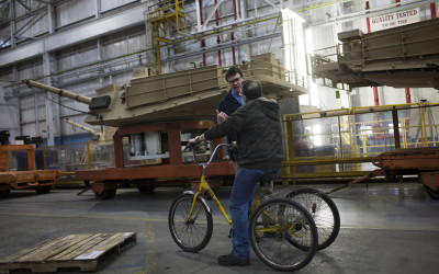 Workers use tricycles to move around the large plant.