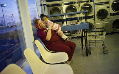 Mother with her child at the laundromat, out of downtown in a strip mall close to the interstate highway.