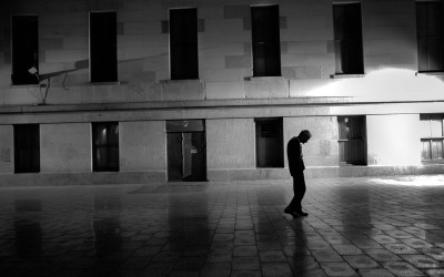 A man walks slowly through Mint Plaza.