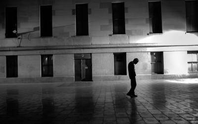A man walks slowly through Mint Plaza.