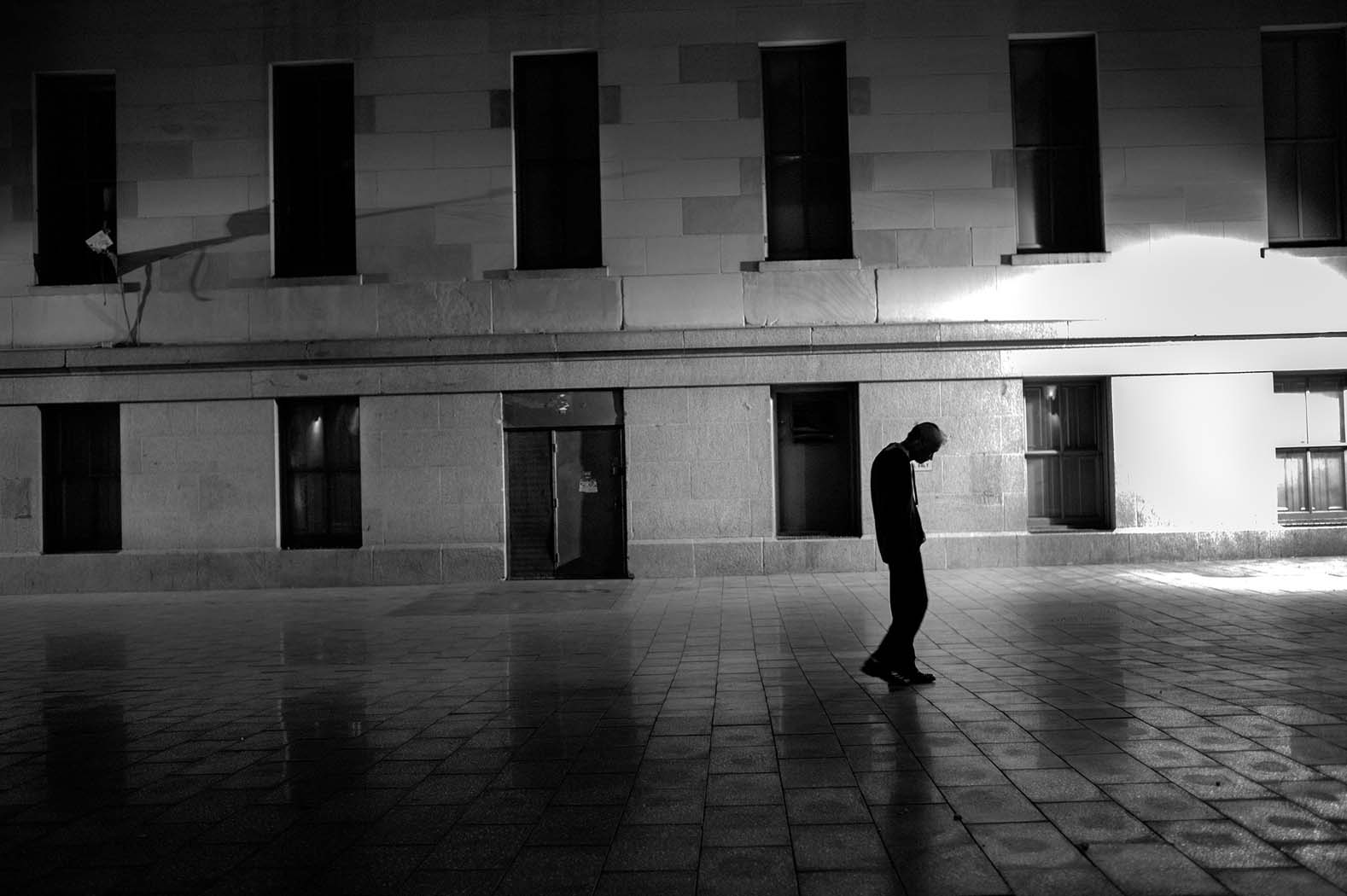 A man walks slowly through Mint Plaza
