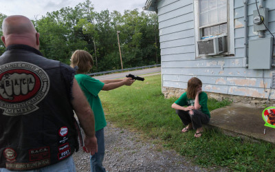 James practices his aim with a new pellet gun under the watchful eye of a member of B.A.C.A (Bikers Against Child Abuse).