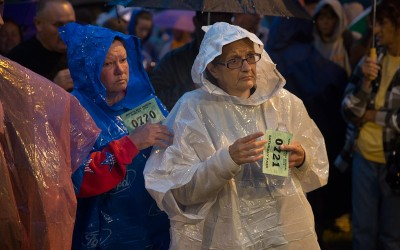 Two women wait for their numbers to be called as they wait before sunrise in the rain with hundreds of other people for free medical care.