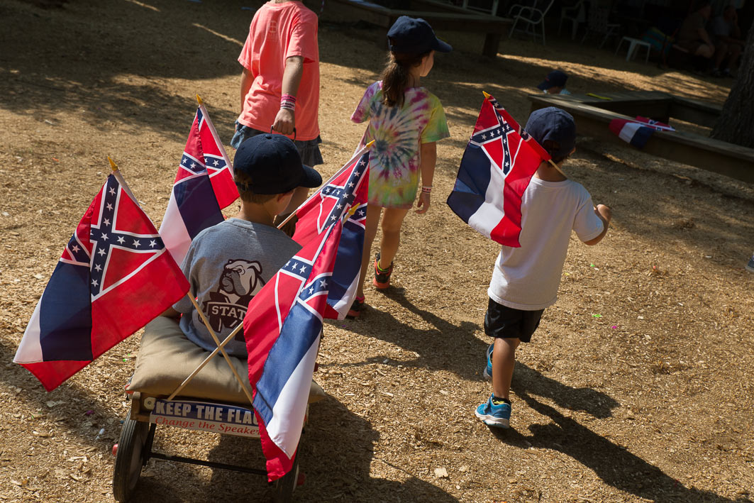 "Kids ride a wagon emblazoned with Mississippi Flags during ""Political Speaking"" on Founders Square at the Neshoba County Fair."