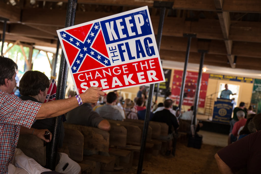At the Neshoba County Fair   Mississippi House Speaker Philip Gunn speaks as protestors hold up signs calling for his removal because he supported changing the  Mississippi flag.