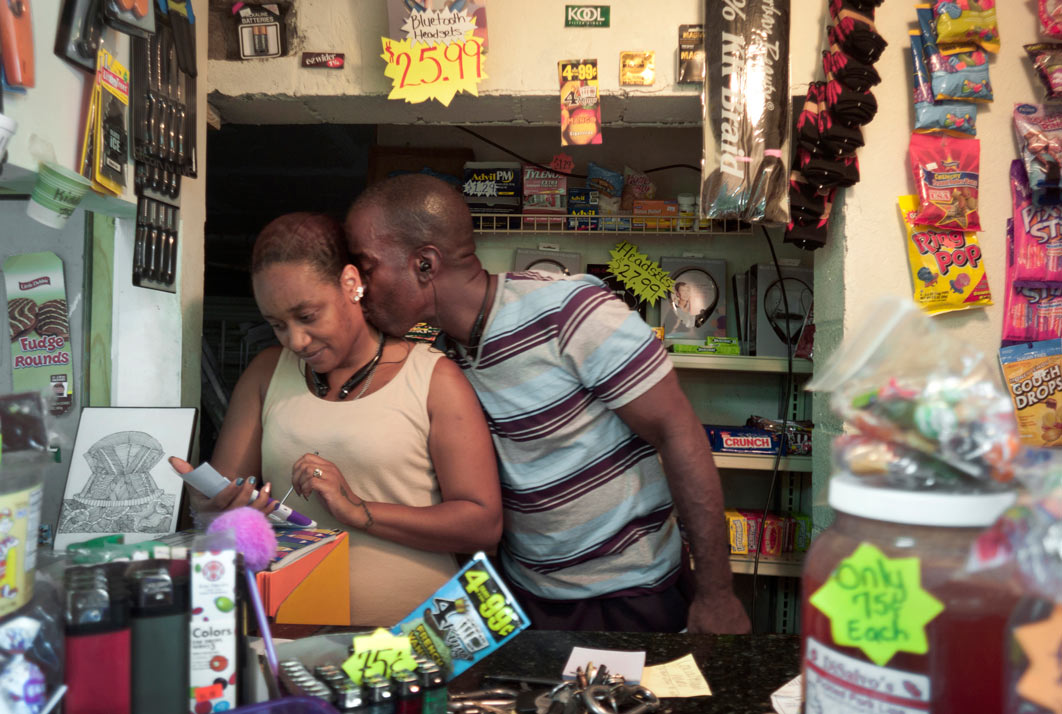 Planting a quick kiss on his wife's neck, Burnell Cotlon and his wife Keasha work behind the counter of their Lower Ninth Ward Market. Using their savings, they bought the flood building that was destroyed by Hurricane Katrina. Burnell and Keasha refer to the store as a mini-Costco because it has a little bit of everything. His mother, Lillie Cotlon, works in the concession stand and helps stock shelves. Before the store opened, Keasha would drive elderly residents or unemployed mothers with children miles to the nearest grocery store who otherwise would have had to ride long distances on slow city buses just to buy food.